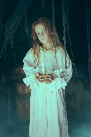 Halloween. A ghost girl in a nightgown wanders through the old house at night. Stok Fotoğraf