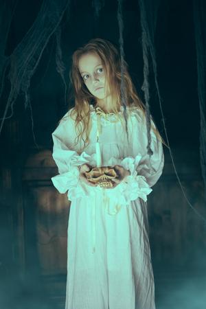Halloween. Ein Geistermädchen im Nachthemd wandert nachts durch das alte Haus.