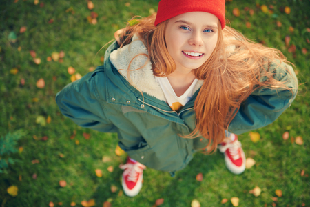 Joyful child girl stands on a grass under autumn leaf fall. Happy autumn mood.