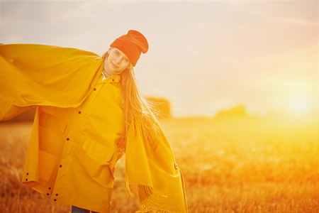 Happy child girl in bright yellow raincoat stands in autumn field. Seasonal fashion. Autumn. Stok Fotoğraf