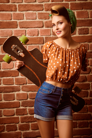 Pin-up girl posing by the brick wall with her skateboard. Pretty woman dressed in pin-up style, with retro hairstyle and make-up.
