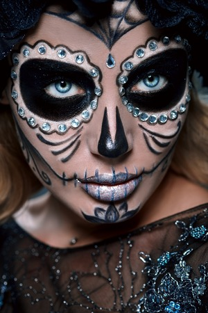 Close-up portrait of Calavera Catrina. Young woman with sugar skull makeup. Dia de los muertos. Day of The Dead. Halloween.