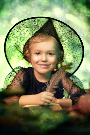 Halloween celebration. Portrait of a cute little girl in witch costume over fairy background with green lights. Stok Fotoğraf