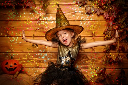 Halloween celebration. Cute little girl in witch costume poses with pumpkins on a wooden background.