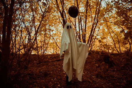 Halloween concept. A ghost child under a white sheet holds black balloon in a forest.