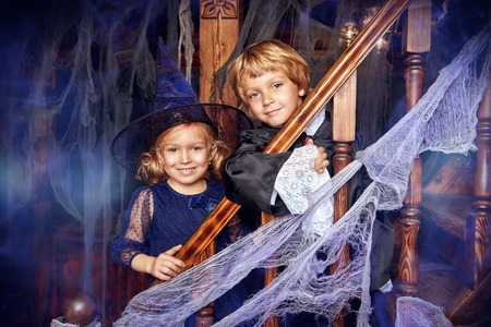 Halloween adventures. Cute little children in carnival costumes celebrate halloween in the old castle. Stok Fotoğraf