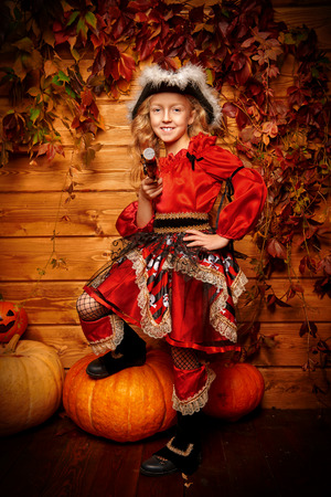 Halloween party. Portrait of a girl in pirate costume. Halloween decorations with pumpkins.