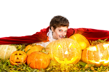 Portrait of a boy dressed in a costume of a vampire with pumpkins over white background. Halloween party with pumpkins.