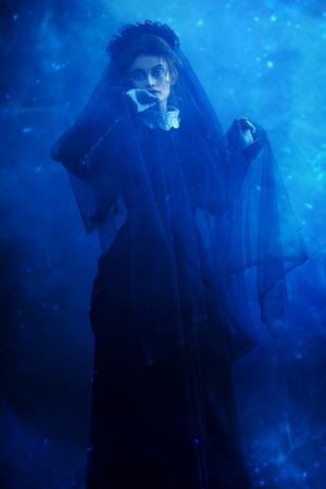 Portret van een Victoriaanse vrouw in rouw. Zwarte weduwe in een sfeer van mysterie en mystiek. Halloween.