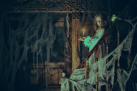 Halloween. A ghost girl in a nightgown wanders through the old house at night. Banque d'images - 131659983