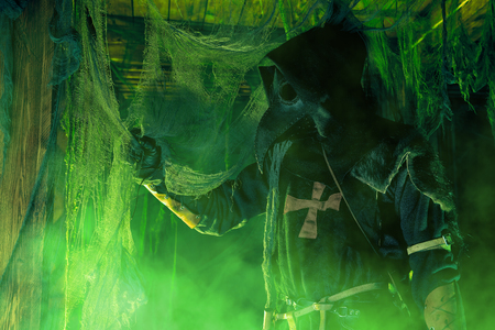 The plague doctor stands in an old house surrounded by a mysterious green light. Halloween.