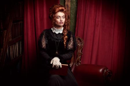 Ricostruzione storica dell'epoca vittoriana. Ritratto di una donna elegante in abito vintage e acconciatura che legge un libro nella sua biblioteca. epoca barocca.