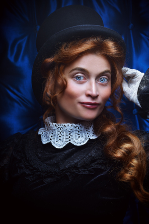 Portrait of an elegant Victorian woman in black dress and top hat. Steampunk theme. The history of makeup and hairstyles.