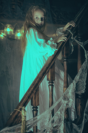 Little girl ghost in a nightgown wanders through the old house at night. Halloween. Reklamní fotografie
