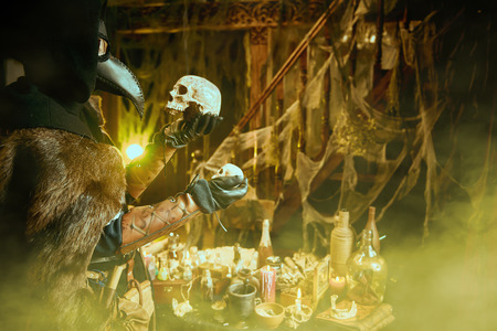 The plague doctor is working at his desk, inventing a cure for bubonic plague. The atmosphere of mysticism. Historical reenactment. Halloween.