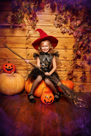 Halloween celebration. Cute little girl in witch costume poses with broom and pumpkins on a wooden background.