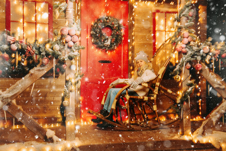 A young cute girl is outside of the house. Merry Christmas, Happy New Year. Miracle time.