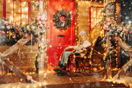 Une jeune fille mignonne est à l'extérieur de la maison. Joyeux Noël heureuse nouvelle année. Le temps des miracles.