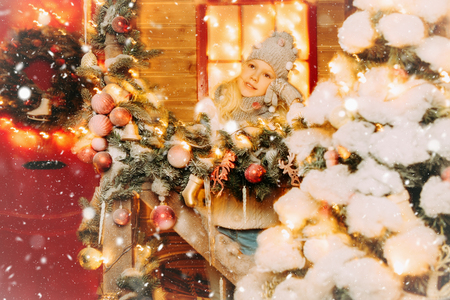 A portrait of a pretty girl on the porch in front of the house decorated for Christmas. Merry Christmas and Happy New Year. Stock Photo