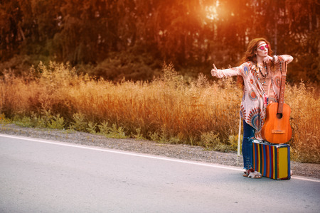 Hitchhiking girl. Beautiful hippie girl standing on a highway and catching a passing car. Spirit of freedom. Fashion shot. Bohemian, bo-ho style. Stok Fotoğraf