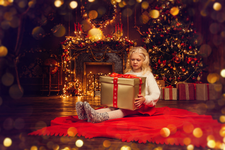 A beautiful girl is at home glad with the gift box she got. Merry Christmas, Happy New Year. Miracle time. Reklamní fotografie