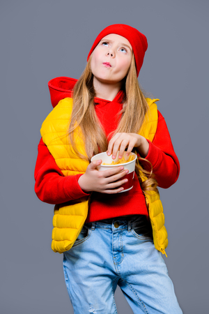 A pretty girl in bright casual clothes eating French fries. Beauty, fashion for kids. Stok Fotoğraf