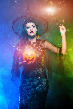 A beautiful lady in a costume of witch holding a pumpkin and magic stick. Halloween. Celebration. Stock Photo