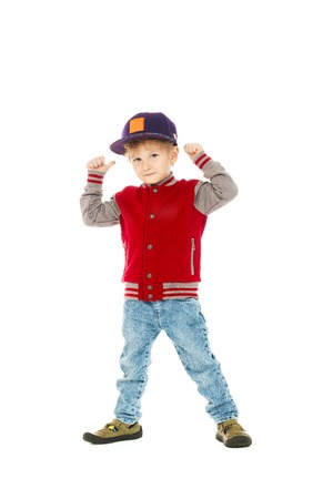 A full length portrait of a happy young schoolboy posing in the studio over the white background. Kids casual fashion, education.