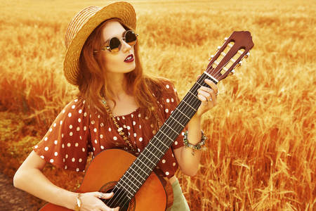 Happy hippie girl stands in a wheat field with her guitar. Spirit of freedom and independence. Banco de Imagens