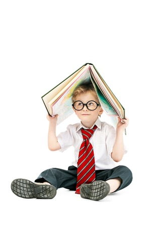 A portrait of a smiling young schoolboy with a notebook. Kids fashion for school, stationery, education.