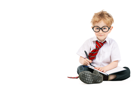 A portrait of a smiling young schoolboy writing in the notebook. Kids fashion for school, stationery, education.