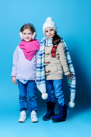 A full length portrait of cute little girls posing in the studio over the light-blue background. Winter fashion for kids. Stockfoto