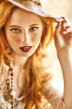 Portrait of a beautiful girl with red hair. Bright light in the background. Hippie and modern bohemian style.