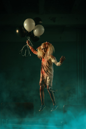 A scary zombie girl  is holding balloons and jumping. Halloween. Horror film. Stock Photo