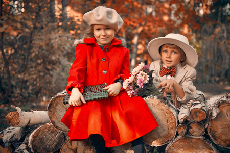 Little boy gentleman presents flowers to his little lady in a beautiful autumn park. Children's fashion. Retro style.