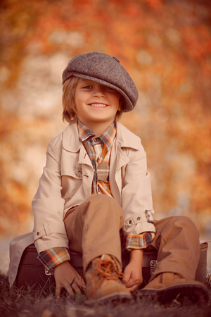 Happy little boy sits on his old fashioned suitcase in a beautiful autumn park. Retro style. Children's fashion.
