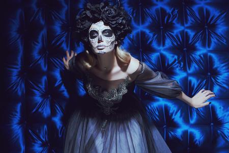Portrait of a beautiful Calavera Catrina. Fashion model with sugar skull makeup. Dia de los muertos. Day of The Dead. Halloween.