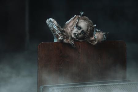 Un retrato de una chica zombie rubia aterradora en una cama. Víspera de Todos los Santos. Película de terror.