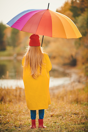 Child girl in bright autumn clothes stands at the autumn park with large multi-colored umbrella and looks into the distance. Mood of autumn. Stock Photo