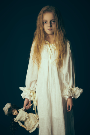 Scary little girl ghost in a white nightgown holds her doll. Black background. Halloween. Imagens