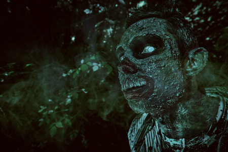 Portrait of a horrible bloody zombie in the night forest. Halloween. Thriller. 写真素材