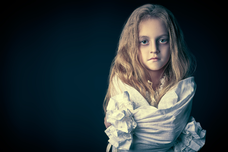 Portrait of a scary little girl ghost in a white nightgown. Black background. Halloween.