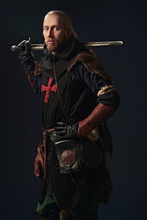 Portrait of a medieval knight in armour and with a sword over black background. Knight Templar. Historical reenactment. Stok Fotoğraf