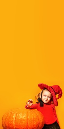Halloween. Funny little girl in a witch costume poses with a big pumpkin over yellow background. Copy space. Stock Photo