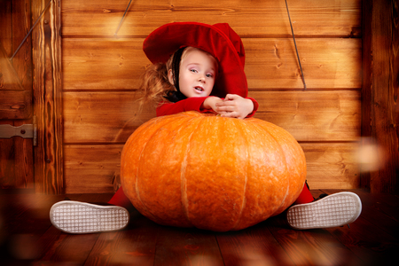 Funny little girl in a witch costume sits behind a big pumpkin over wooden background. Halloween. Stock Photo