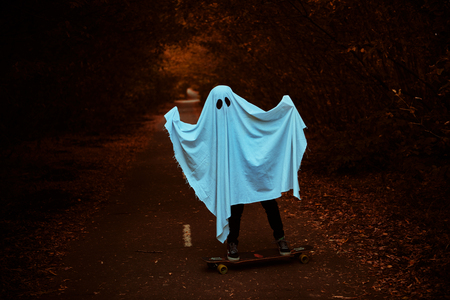 A child boy boy in a ghost costume rides on a skateboard on the road in the park. Halloween party. Stock fotó