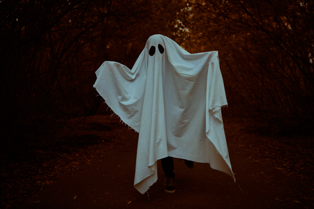 A lonely ghost of a child under a white sheet stands on a deserted road in the forest. Halloween. Stock fotó