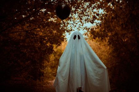 Notion d'Halloween. Un enfant fantôme sous un drap blanc tient un ballon noir dans une forêt.