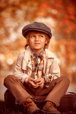 Happy little boy sits on his old fashioned suitcase in a beautiful autumn park. Retro style. Childrens fashion.