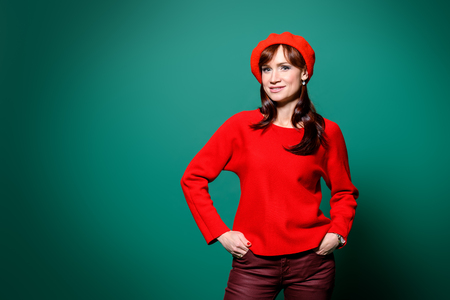 A portrait of a beautiful woman in red casual clothes posing over the green backgound in the studio. Beauty, fashion.